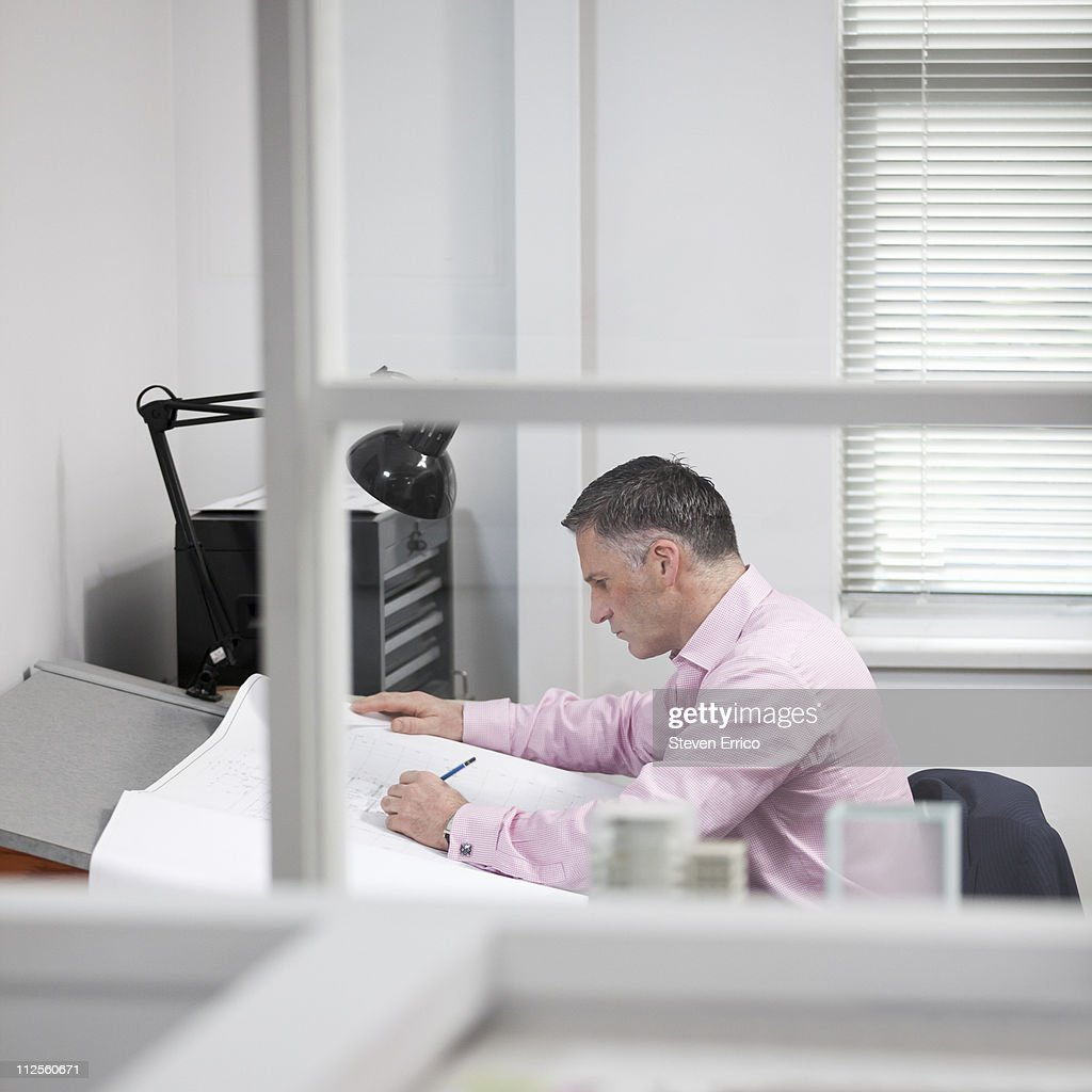 Architect studying blueprints in office : Stock Photo