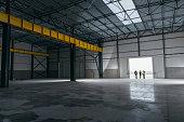 Architect team At Work Site With Blueprints standing at big hangar doors