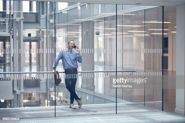 Architect using cell phone in office hallway