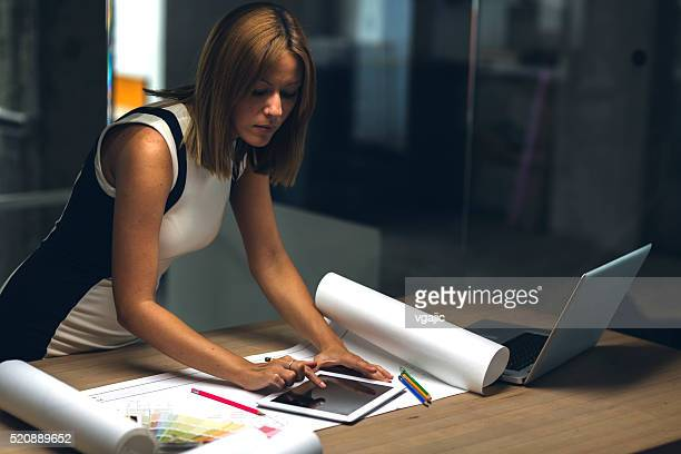 Architect using digital tablet late in her office.