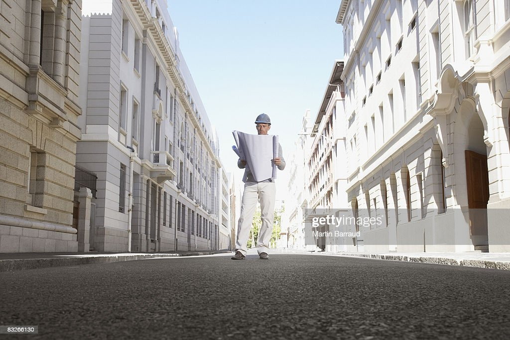 Architect with blueprints standing on urban street : Stock Photo