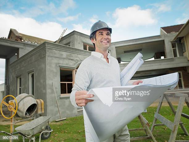 Architect with blueprints standing outside house under construction