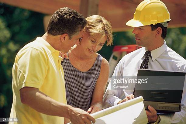 Architect with couple at construction site