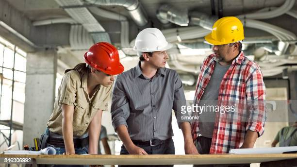 Architect with male and female foreman discussing plans on table at construction site
