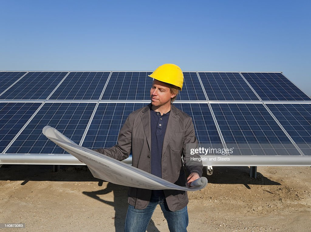 Architect with solar panels blueprints stock photo getty for Solar panel blueprint