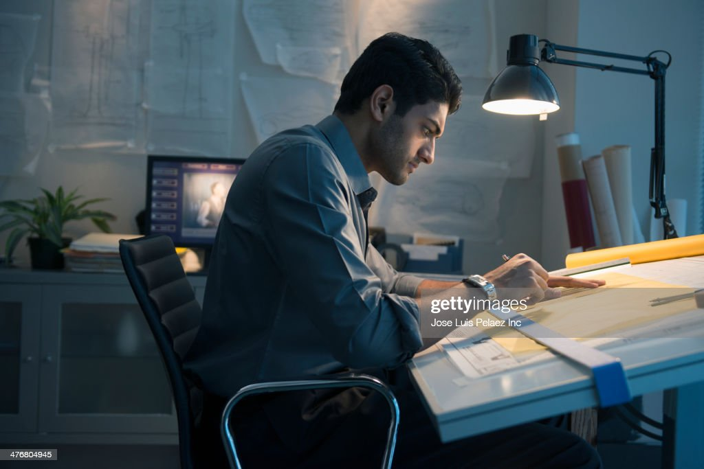 Architect working at drafting table in office : Stock Photo