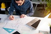 Architect working in office with house project on desk