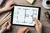 Team of architects working on the house project on a wooden table. Top view of hands pointing architectural project on digital tablet. Interior designer hand working with digital tablet.