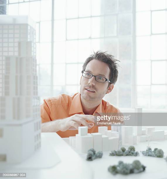 Architect working with scale model of office building and plaza