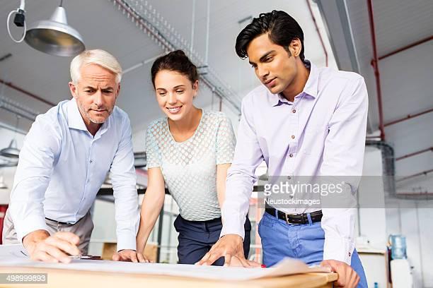 Architects Analyzing Blueprint At Desk