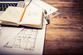 Open notepad on an architect desk showing a hand drawn facade and plan