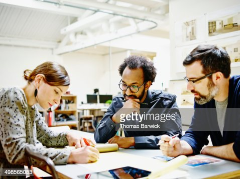Architects examining project plans in office