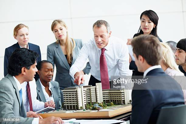 Architects in discussion about building model