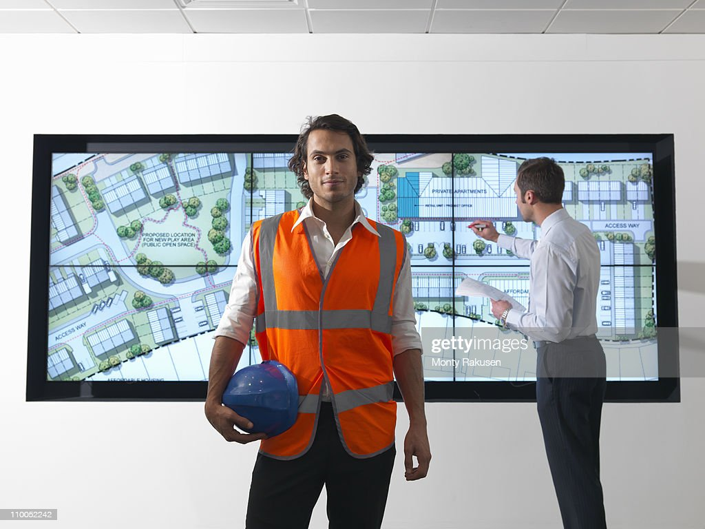 Architects in front of plans on screen : Stock Photo