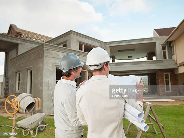 Architekten in harten-Werkzeuge und Mützen, die sie suchen im Haus