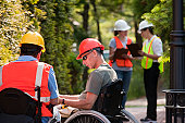 Architects in wheelchairs discussing data before meeting with project engineers