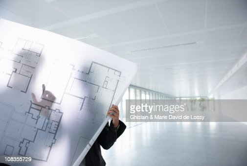 Architects looking at blue prints : Stock Photo