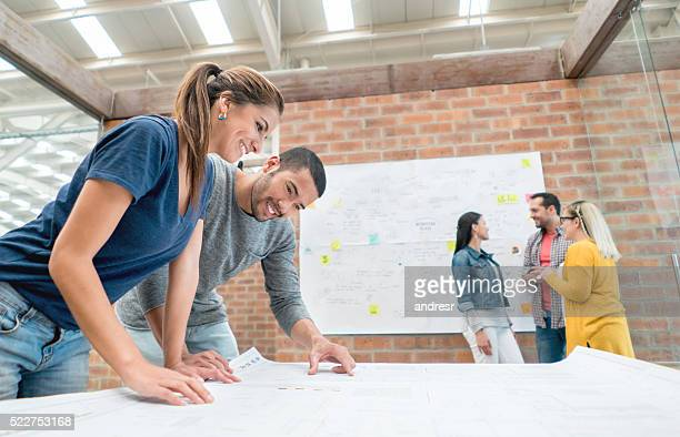Architects looking at blueprints at the office