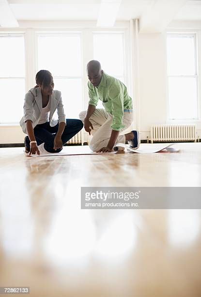 Architects looking at blueprints in empty room