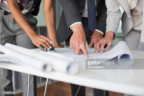 Architects looking at blueprints in office