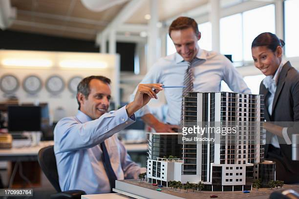 Architects looking at building model in office