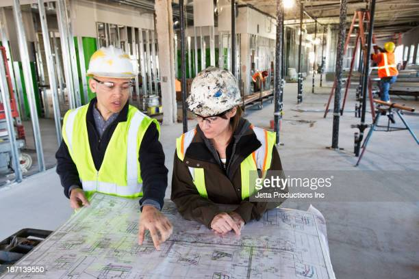 Architects reading blueprints at construction site