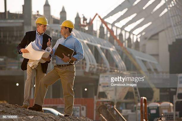 Architects with blueprints at construction site