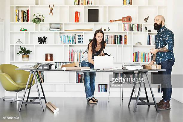 Architects working at table against bookshelf in home office