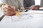 Architects working on blueprint. Architects workplace - architectural project, blueprints, ruler, calculator, laptop and divider compass. Construction concept. Engineering tools.