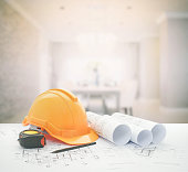 architectural blueprint with safety helmet and tools over modern luxury dining room interior.