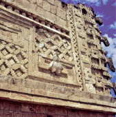 Architecture detail showing a relief sculpture of a human headed bird and a mask column at the Nunnery Quadrangle in Uxmal Mexico
