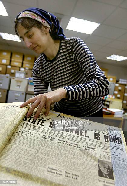 Archivist Elaine Moshe pages through an original edition of The Palestine Post from May 14 1948 which announces the birth of the State of Israel in...