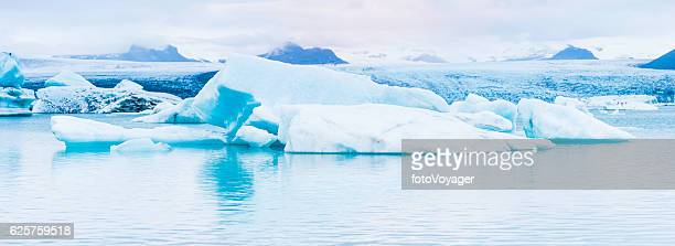 Arctic icebergs gleaming white in ocean lagoon panorama Jokulsarlon Iceland