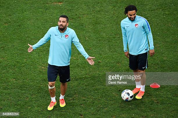 Arda Turan and Selcuk Inan of Turkey react during a training session ahead of their UEFA Euro 2016 Group D match against Spain at Allianz Riviera...
