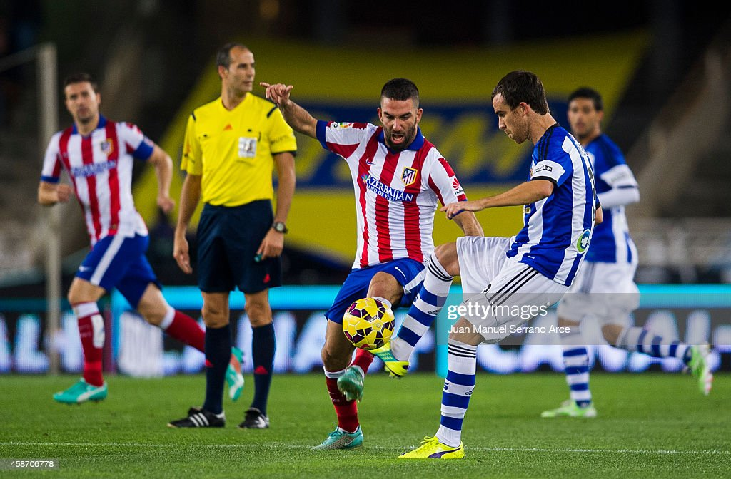 Arda Turan of Atletico de Madrid duels for the ball withÊMikel Gonzalez of Real Sociedad during the La Liga match between Real Sociedad andÊAtletico...