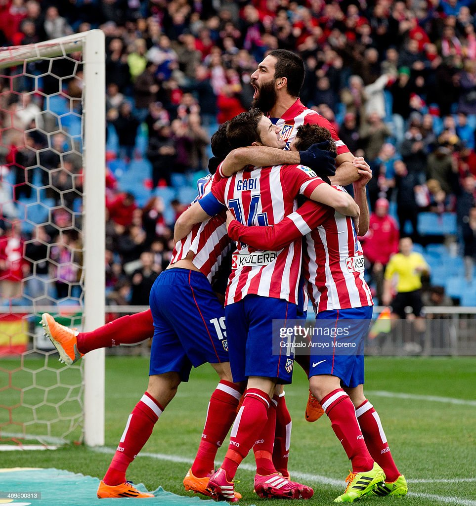 Arda Turan of Atletico de Madrid jumps over his teammates celebrating Diego Costa«s (L) goal during the La Liga match between Club Atletico de Madrid and Real Valladolid CF at Vicente Calderon Stadium on February 15, 2014 in Madrid, Spain.