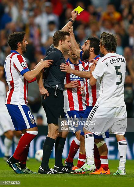 Arda Turan of Atletico Madrid grabs the arm of referee Felix Brych as he is shown a second yellow card and is sent off during the UEFA Champions...