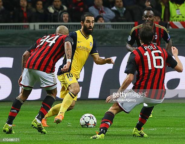 Arda Turan of Atletico Madrid vies for the ball with Nigel De Jong and Andrea Poli of Milan during the UEFA Champions League round of 16 soccer match...
