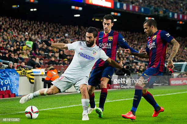 Arda Turan of Club Atletico de Madrid controls the ball next to Sergio Busquets and Dani Alves of FC Barcelona during the Copa del Rey QuarterFinal...