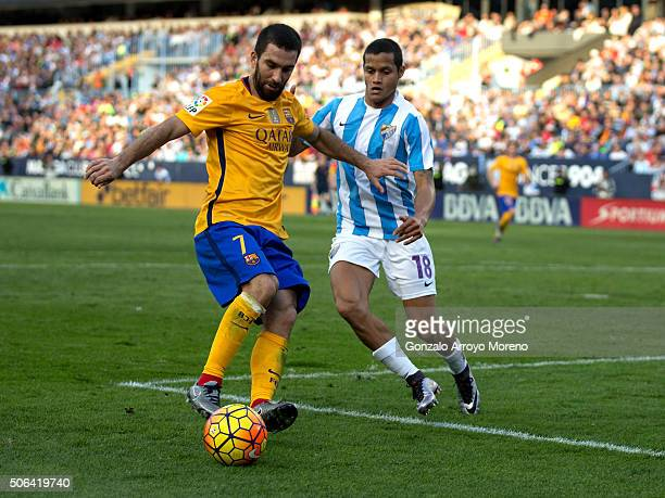 Arda Turan of FC Barcelona competes for the ball with Roberto Rosales of Malaga CF during the La Liga match between Malaga CF and FC Barcelona at La...