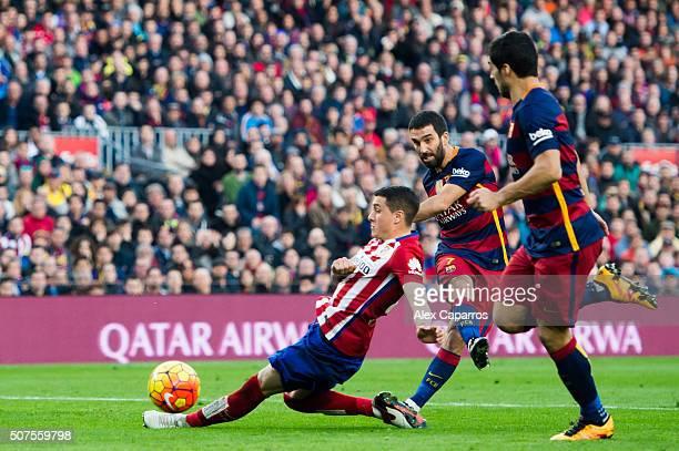 Arda Turan of FC Barcelona kicks the ball between Jose Maria Gimenez of Club Atletico de Madrid and Luis Suarez of FC Barcelona during the La Liga...