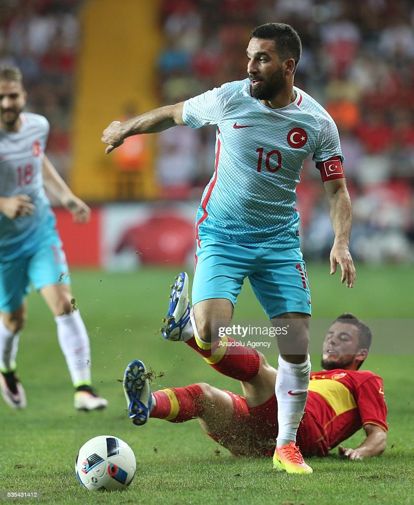 Arda Turan (front) of Turkey and Jovovic (rear) of Montenegro vie for the ball during the friendly football match between Turkey and Montenegro at Antalya Ataturk Stadium in Antalya, Turkey on May 29, 2016.