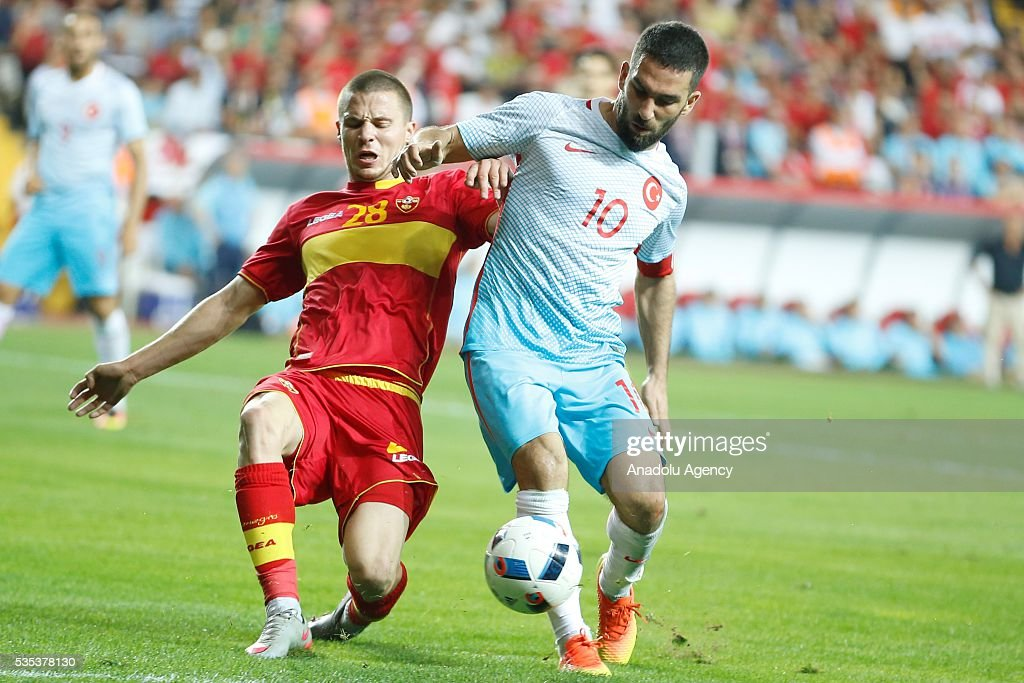 Arda Turan (R) of Turkey and Sofranac (L) of Montenegro vie for the ball during the friendly football match between Turkey and Montenegro at Antalya Ataturk Stadium in Antalya, Turkey on May 29, 2016.