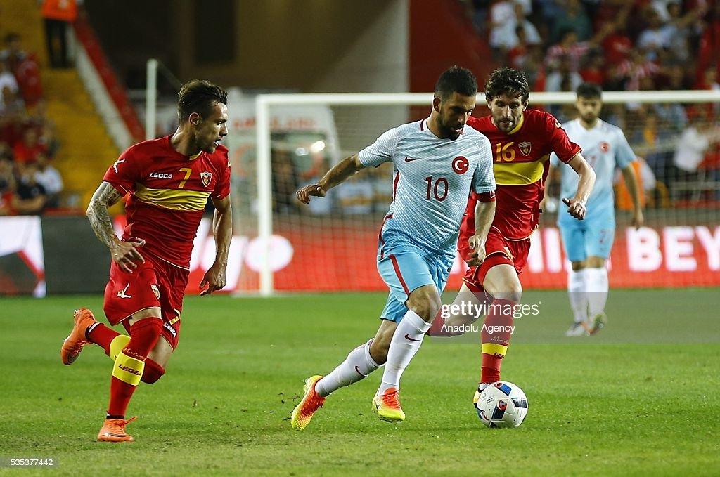 Arda Turan (C) of Turkey vies for the ball during the friendly football match between Turkey and Montenegro at Antalya Ataturk Stadium in Antalya, Turkey on May 29, 2016.