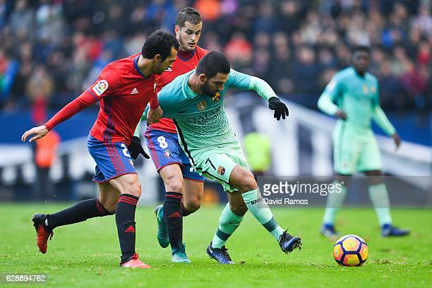 Ardan Turan of FC Barcelona competes for the ball with Miguel de las Cuevas and Goran Causic of CA Osasuna during the La Liga match between CA...