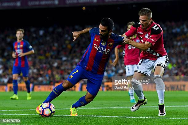 Ardan Turan of FC Barcelona competes for the ball with Raul Garcia of Deportivo Alaves during the La Liga match between FC Barcelona and Deportivo...