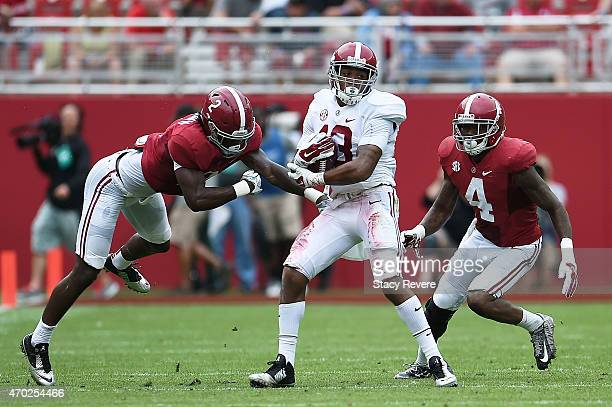 ArDarius Stewart of the White team is pursued by Tony Brown and Eddie Jackson of the Crimson team during the University of Alabama A Day spring game...