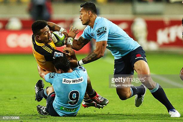 Ardie Savea of the Hurricanes is tackled by Nick Phipps and Israel Folau of the Waratahs during the round 10 Super Rugby match between the Hurricanes...