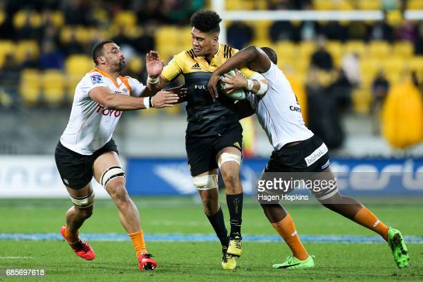 Ardie Savea of the Hurricanes is tackled by Uzair Cassiem and Oupa Mohoje of the Cheetahs during the round 13 Super Rugby match between the...