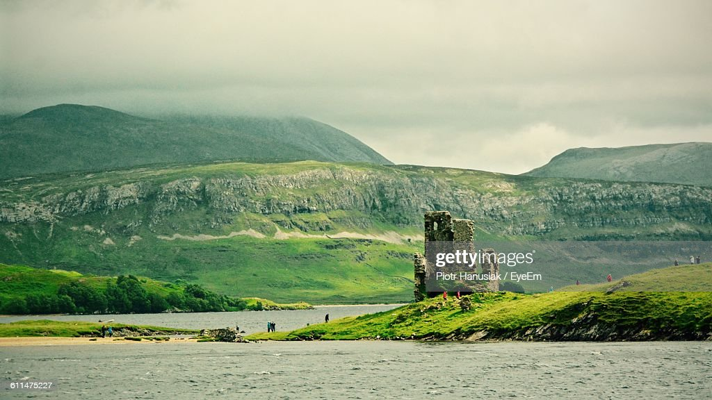 Ardvreck Castle By Lake Against Cloudy Sky